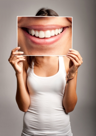 Photo pour young woman holding a picture of a mouth smiling - image libre de droit