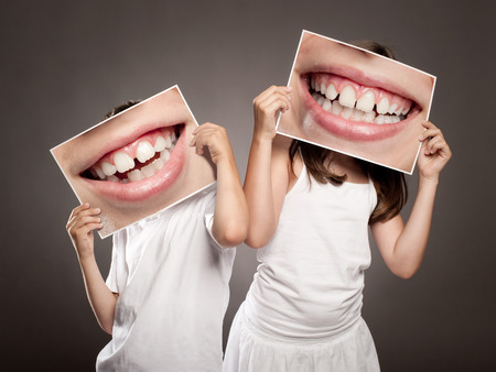 Photo pour two children holding a picture of a mouth smiling - image libre de droit