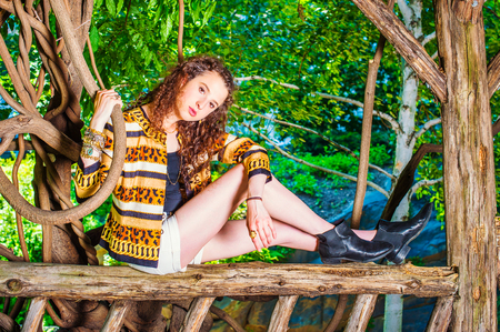 American teenage girl with curly hair wearing patterned fashionable jacket, short pants, bracelet, boot shoes, sitting on wooden fence, hand holding rattan, inclining head, relaxing, thinking.