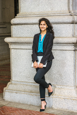 Photo pour East Indian American college student studying in New York, wearing black blazer, blue shirt, striped pants, heels, holding laptop computer, standing against column, smiling. - image libre de droit
