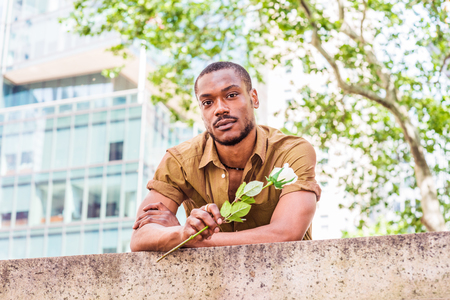 Photo pour Young African American Man missing you, waiting for you in New York, wearing green short sleeve shirt, holding white rose, back bending forward on top of wall by street in Manhattan, looking forward. - image libre de droit