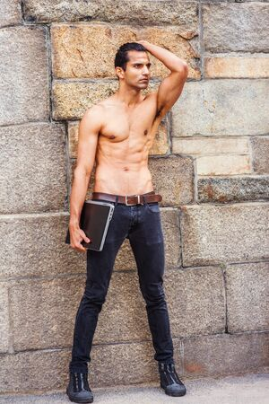 Photo pour Young East Indian American Man, half naked, showing strong body, wearing black jeans, sneakers, holding laptop computer, standing by rock wall in New York, looking forward. - image libre de droit
