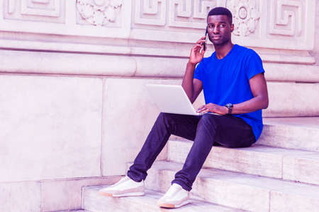 Photo for Young African American College Student studying in New York, wearing blue T shirt, black pants, sneakers, wristwatch, sitting on stairs on campus, working on laptop computer, talking on cell phone. - Royalty Free Image