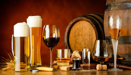 Photo pour alcoholic drinks on wooden table in glasses, mugs and shots with barrel in background - image libre de droit