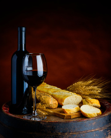 Glass and bottle of red wine, baguettes and wheat in a rustical setup