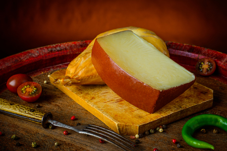 Cheese and food on a wooden rustic table with tomatoes and pepper sin still life