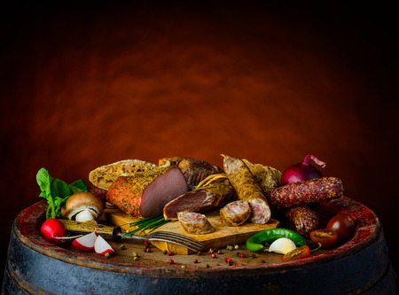Rustic food with meat, smoked meat and sausages, vegetables, mushrooms on wooden chopping-board