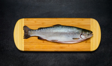 Raw Freshwater Trout Fish on Wooden Chopping board and on Dark Background