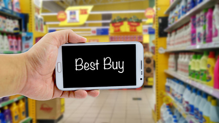 image concept, cropped hand holding smartphone with word BEST BUY over blurred hypermarket background