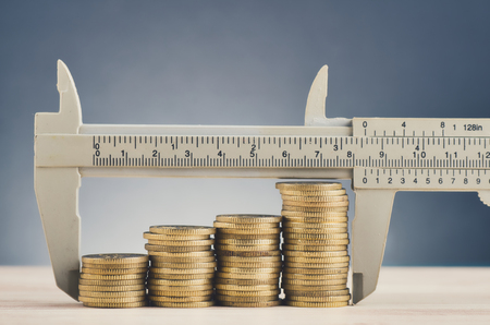 Photo pour financial crisis and saving money concept,vernier caliper and stacking coins on wooden desk over beautiful reverberation gradient background - image libre de droit