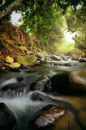 Photo pour Beautiful tropical waterfall in lush surrounded by green forest.wet rock and moss.selective focus shot. - image libre de droit