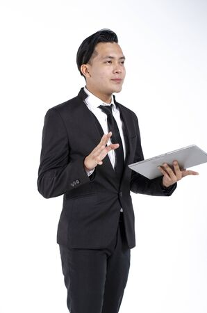 Photo for Young business man wearing black suit holding tablet against white background - Royalty Free Image