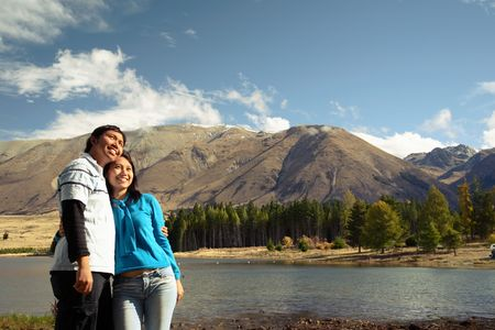 Lake and a couple standing enjoying beautiful view of New Zealand mountains