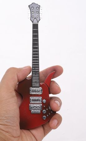 Isolated miniature of red electric guitar held by a hand over white background