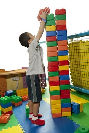 Foto de A little boy seriously build tower block - Imagen libre de derechos