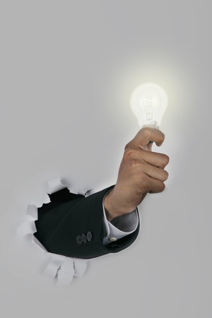 Businessman hand breaking through a paper wall holding an illuminated light bulb