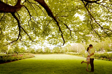 Asian young couple kissing under treeの写真素材