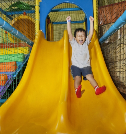 Happy little boy sliding on playground