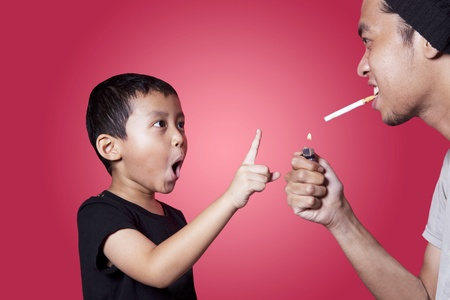 Cute boy give warning to a smoker isolated on red
