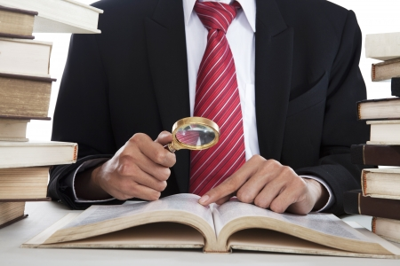 Businessman searching informations from the books by using magnifying