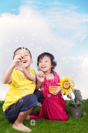 Happy sibling playing soap bubbles on the green grass