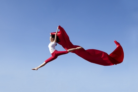 Young asian woman jumping with red scarf shot over clear blue sky
