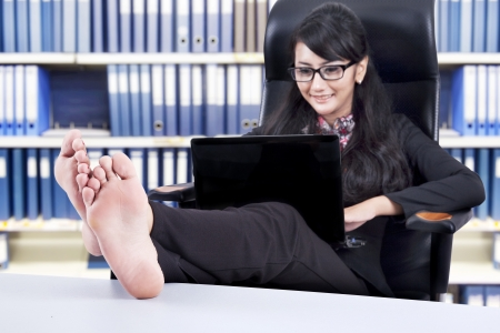 Successful Businesswoman using laptop with Feet Up on a Table, shot in the officeの写真素材