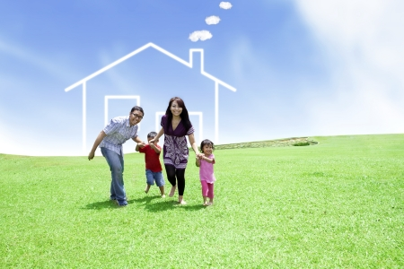 Happy family running on field with a drawn house in background