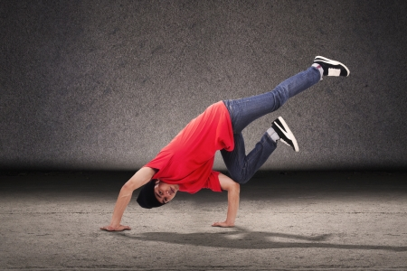 Young breakdancer doing a breakdance style in front of grey background