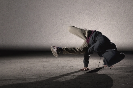 Cool looking dancer breakdancing on grey grunge wall background