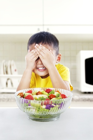 Boy refuses to eat a big portion of salad by cover his eyes. shot in the kitchen