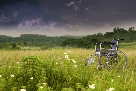 Empty wheelchair in nature symbolizing sadness and loneliness