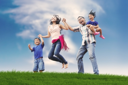 Photo pour Excited and happy asian family jumping in meadow shot during summer - image libre de droit