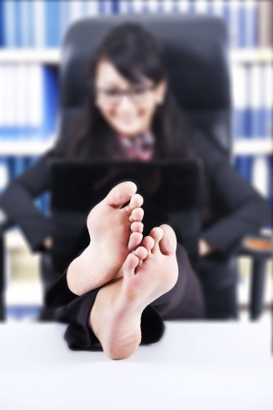 Businesswoman using laptop with Feet Up on a Table, shot in the office
