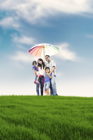 Foto de Happy family with parents and two kids posing in meadow. Father carrying an umbrella symbolizing protection for the whole family. - Imagen libre de derechos