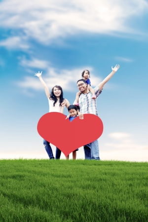 Happy Asian family carrying a heart cutout with copy space in meadow.