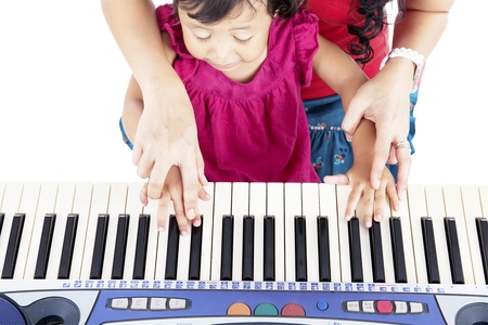 Portrait of asian little girl playing piano with her mother guiding her hands