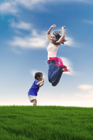 Photo pour Portrait of happy mother and her daughter jumping on the meadow. shot outdoor during summer - image libre de droit
