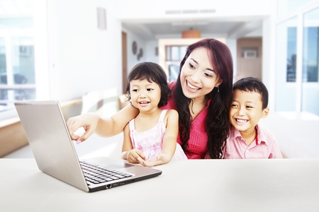 Happy young mother with her children using ultrabook laptop computer to enjoy entertainment at home