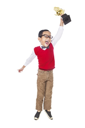 A young happy elementary student holding a trophy and jump to celebrate his success. isolated on white