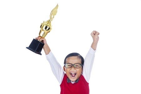 A young happy elementary student holding a trophy and celebrate his success. isolated on white