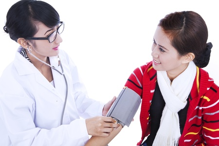 Female doctor checking blood pressure of her patient isolated in white