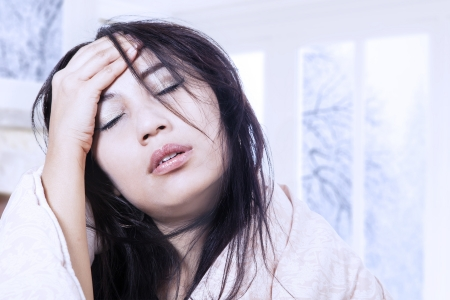 Asian woman is having a headache with fever at home