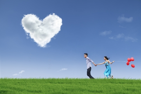 Photo pour Happy couple is running together in green field while holding red balloons - image libre de droit