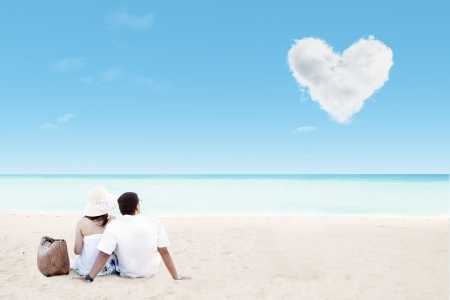 Beautiful couple by the beach with clouds of heart