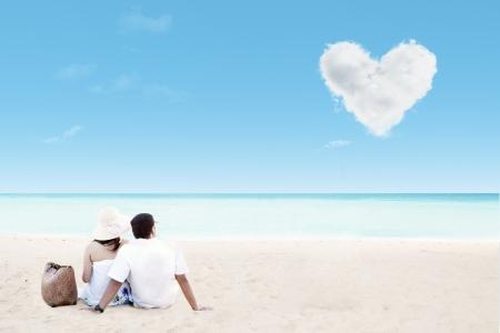 Foto de Beautiful couple by the beach with clouds of heart - Imagen libre de derechos