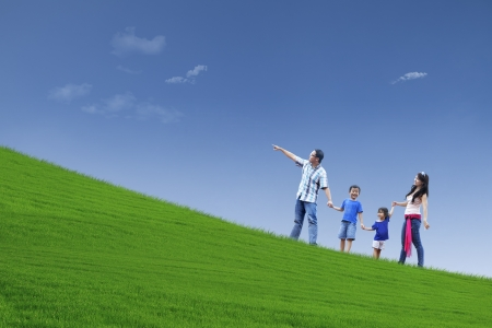 Happy family walking on the hill to see beautiful landscape