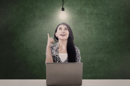 Beautiful businesswoman under a lit light bulb while working with her laptop