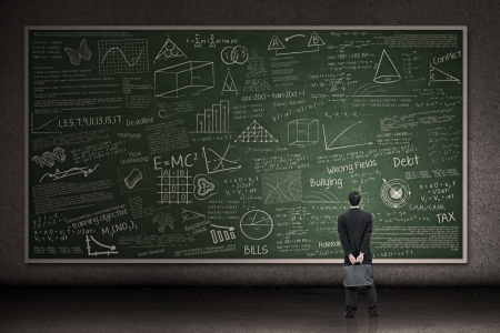 Photo pour Businessman is looking at a huge hand drawn chalkboard in a classroom - image libre de droit