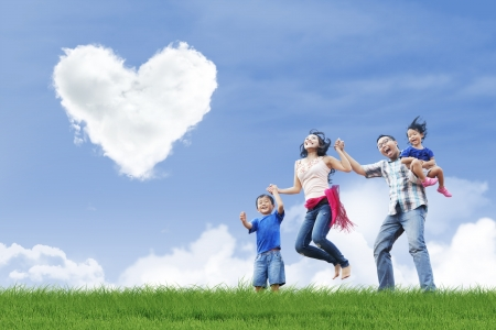 Happy family is having fun under love shape clouds in the park